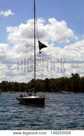 HARBOR SPRINGS, MICHIGAN / UNITED STATES - AUGUST 1, 2016: A sailboat approaches the Harbor Springs Municipal Marina.