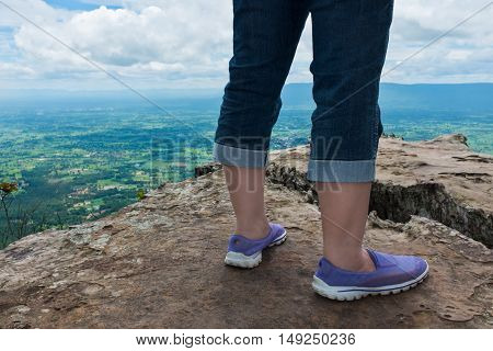 Closeup of tourist's feet on boulder at view point on summer day. Back view of woman hiking accomplishment on the top of the mountain travel on vacation. Motivation and freedom concept.