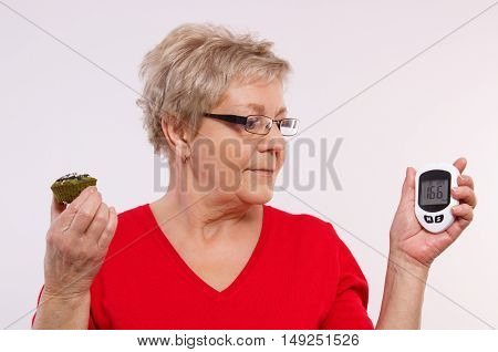 Surprised elderly woman holding glucose meter with bad result of measurement sugar level and fresh cupcake concept of diabetes in old age checking sugar level