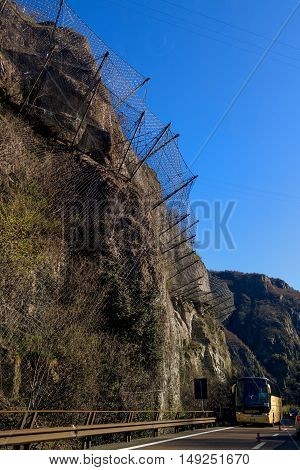 Highway A 27 Italy - April 13 2013: Protection wire mesh against falling rocks from the mountains. On the road the bus rides.