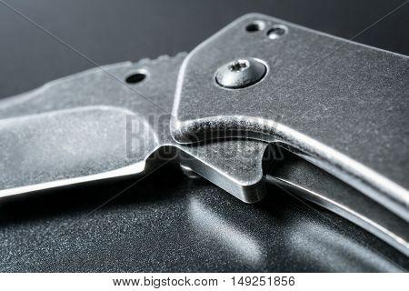 Macro Of A Half Open Black Folding Knife On Dark Ground