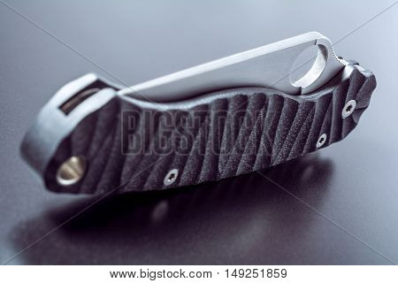 Handle Of A Closed Faint Army Knife Lying On Dark Ground With Reflection