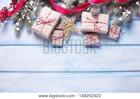 Christmas presents fur tree branches decorative star and red berries on blue wooden background. Selective focus. Top view. Place for text.