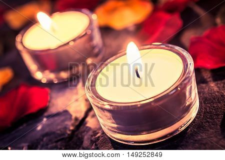 Two Romantic Candles On Slate With Rose Petals And Leafs