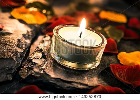 One Romantic Valentine Candle Light On Slate With Rose Petals And Leafs