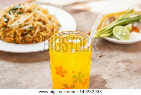 Orange juice in a glass with ice on dining table