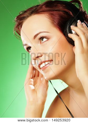 Young happy woman listening to music with headhones over green background