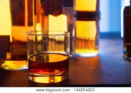 Glass of whiskey on a dim bar counter top,with whisky and bourbon bottles in the background with incoming light. Focus on water line of glass. Shallow depth of field.