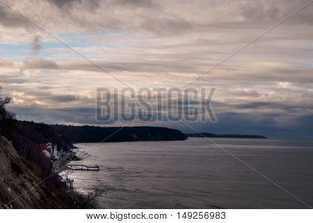 Beach in Svetlogorsk, Kaliningrad. Photo of beautiful panorama view of sea shore, forest and clouuds at sunset.