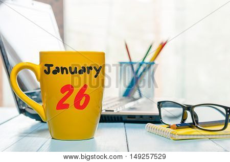 January 26th. Day 26 of month, Calendar on cup morning coffee or tea, author workplace background. Winter at work concept. Empty space for text.