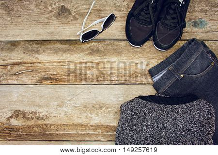 Women's clothing and accessories: grey sweater, jeans, sneakers and sunglasses on wooden background. Top view.