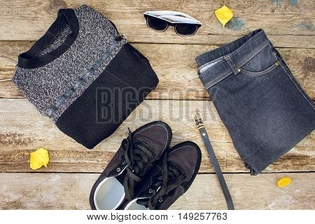 Women's clothing and accessories: grey sweater, jeans, belt, sneakers, sunglasses, yellow leaves on wooden background. Top view.