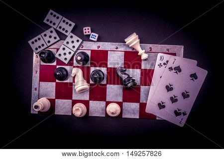 Various board games and figurines over checkers board and dark background. Metaphor for gaming and gambling.
