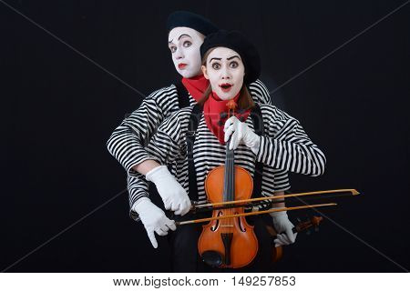wo mime in striped shirts and berets playing the violin