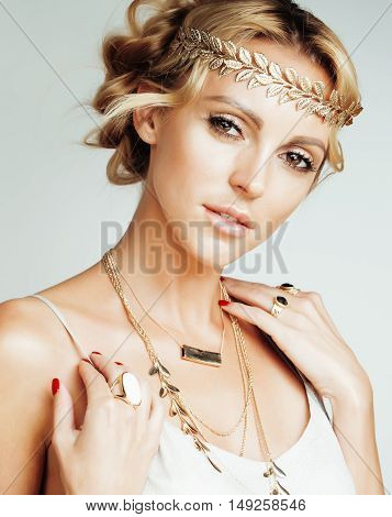young blond woman dressed like ancient greek godess, gold jewelry close up isolated, lifestyle people concept