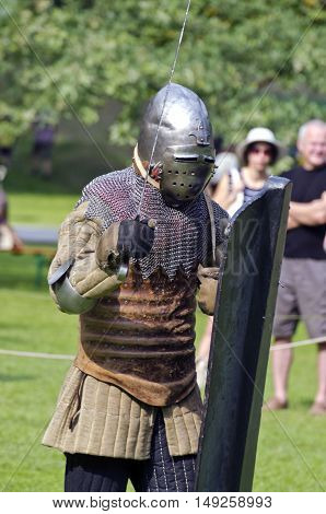 Knight with brownish clothes and armor and shield in medieval festival in town