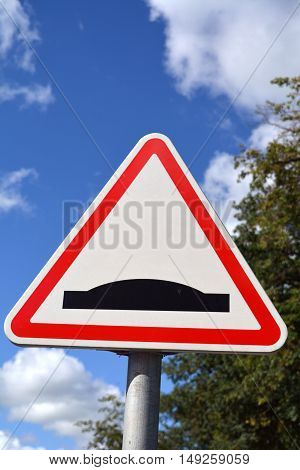 Triangle shaped road sign with red and white and black bump