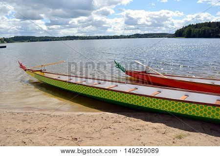 Tourist boats decorated with tails and scale pattern on beach by the lake