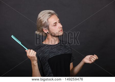 Handsome young fashion model with colored hair highlighted stylish haircut comb in hand
