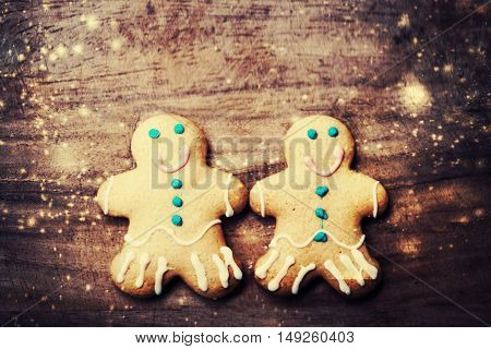 Christmas homemade gingerbread cookies over wooden table. Christmas Card with decorations and falling snow
