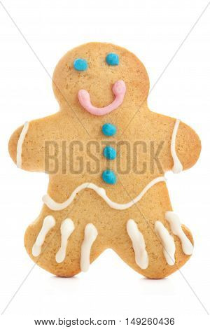 Gingerbread man isolated over white background. Holiday Christmas cookie decorated with colorful icing. Gingerbread man shape macro.