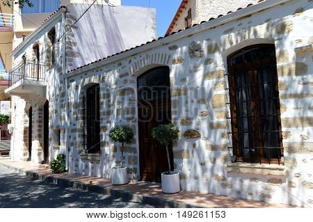 White facade with doors and wooden windows with trees green.