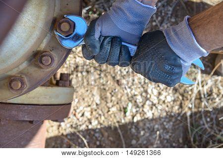 Hands of a workman tighten a bolt.