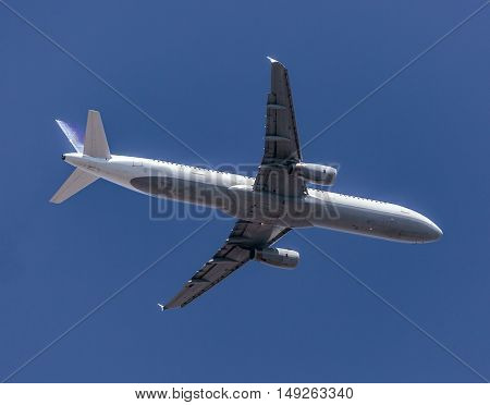 Airplane Against Blue Sky In Flight