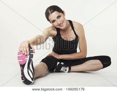 Fit Woman Stretching Her Leg To Warm Up Isolated Over  Background