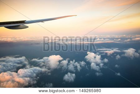 Beautiful view above clouds from airplane perspective with wing in sunset light