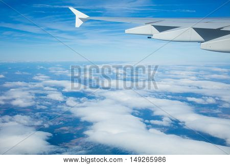 Beautiful view above clouds from airplane perspective with wing