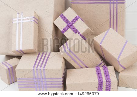 pile of boxes with purple ribbons, white