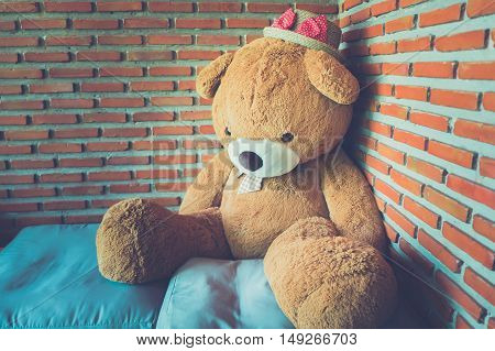 Teddy bear brown toy alone sitting on sofa in brick wall background - Dark tone coler