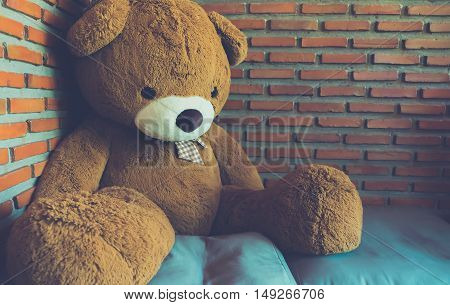 Teddy bear brown toy alone sitting on sofa in brick wall background - Vintage effect style pictures