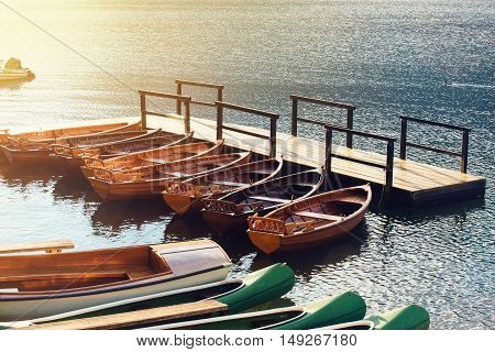 Small wooden boats and canoes docked and tied to empty pier on the lake