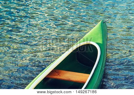 Green plastic canoe on lake in summer afternoon
