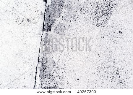 Crack in the concrete pavement as abstract background texture of white painted cement flooring