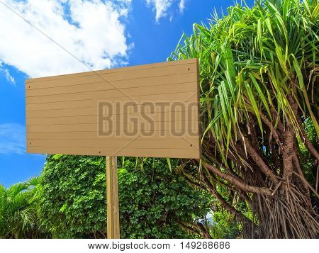 blank rectangular wooden billboard in a tropical garden