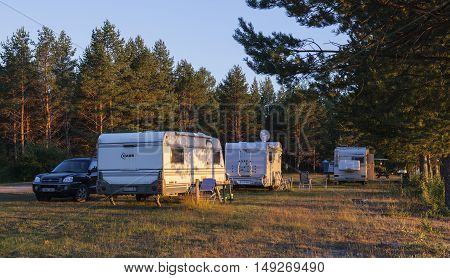 MEDELPAD, SWEDEN ON JULY 09. View of a campsite, car, campers and caravan on July 09, 2016 by Holmsjon, Sweden. Late evening after a sunny day. Pine forest. Editorial use.