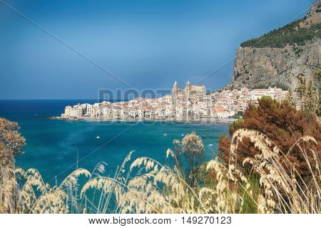 Landscape View on the coastal city of Cefalu on Sicily in Italy. Blue sky and sea. Large rock and medieval tourist town with old cathedral