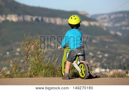 Little Boy Is On A Bike And It Looks The Mountain