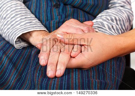 Close up photo of a dedicated caregiver holding an elderly woman's hands