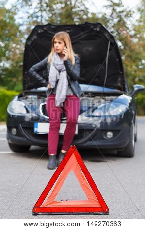 Picture of a helpless young woman on the road with her car broken