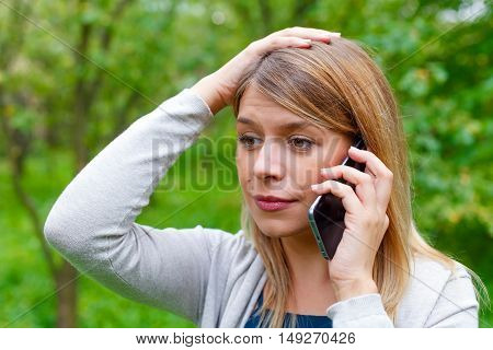 Picture of a worried young woman on the phone