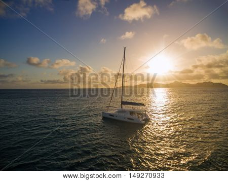 Aerial view of catamaran sailing in coastline with beautiful sunset. Tropical Seychelles island on background