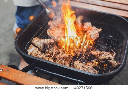 Grill steaks on metal grate with flame. Chef hands cooking roasted juicy meat barbecue with lots of fire. BBQ fresh beef chop slices. Traditional dish on charcoal and flame, picnic, street food