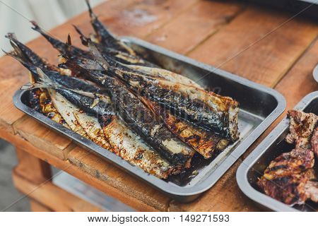 Plenty of roasted mackerel fish, grilled at barbecue in metal tray. Seafood bbq outdoors at picnic, party. Street food, grill takeaway