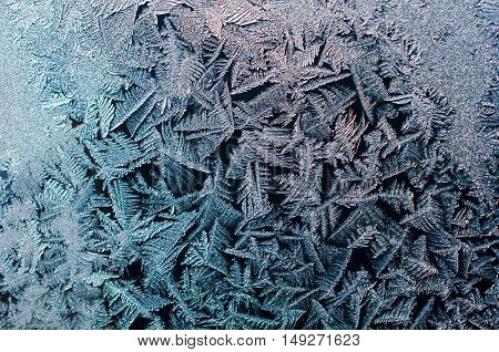 Brilliant ice crystals on window glass in the sunlight on a dark background.WinterJanuary.Winter background.