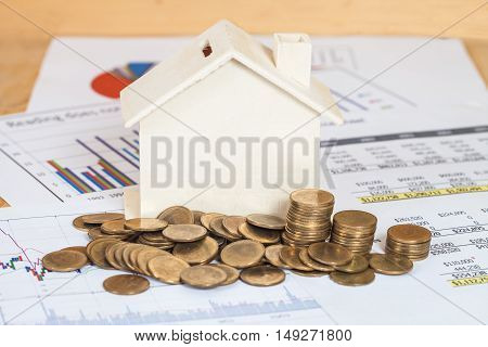 Miniature house with money and business chart