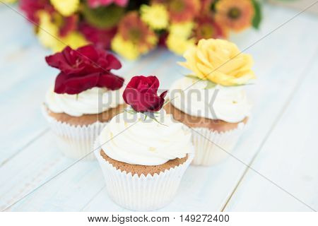Three cupcakes with red and yellow roses. Selective focus